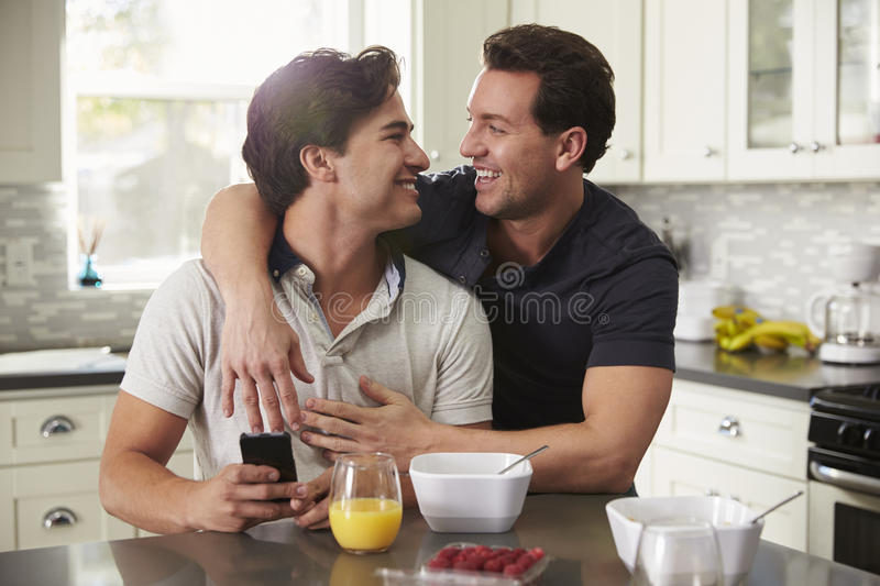 Male gay couple in their 20s embracing in their kitchen royalty free stock image
