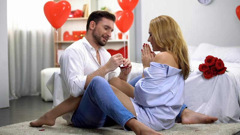 Male giving excited lady engagement ring, romantic surprise on Valentines Day royalty free stock photos