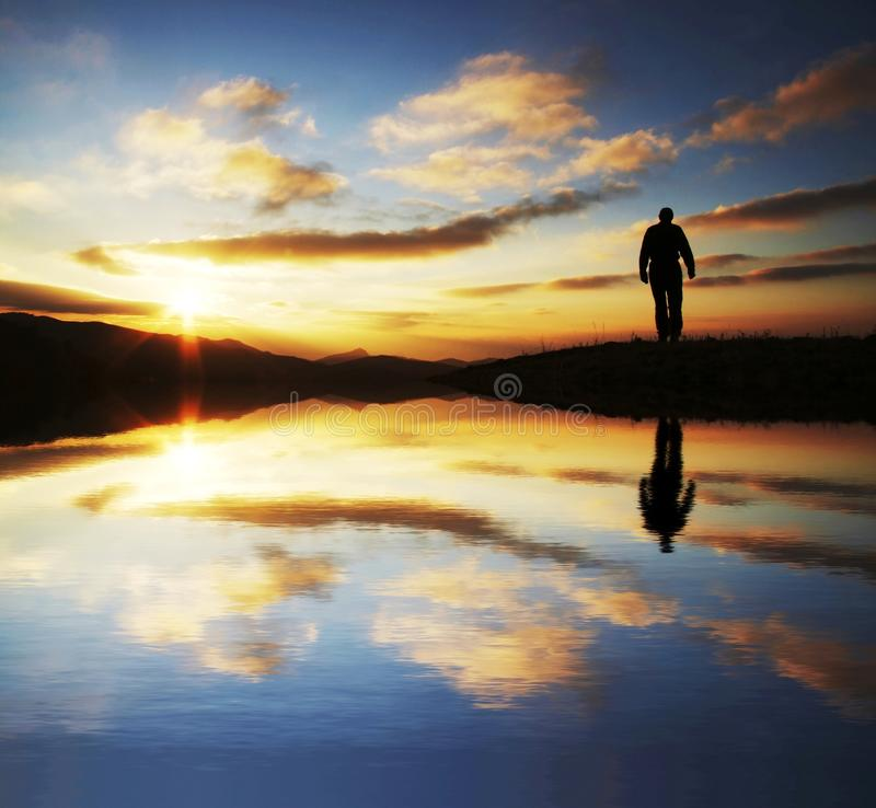 Male going on sunrise. Men silhouette on the sunset background royalty free stock photo