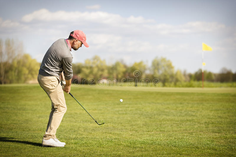 Male golf player pitching near green. stock photo