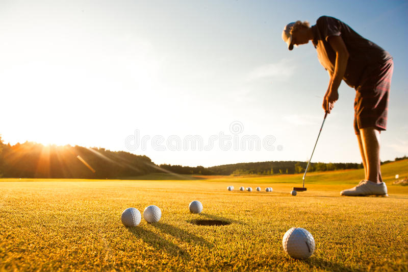 Male golf player practicing a par during sunset stock image