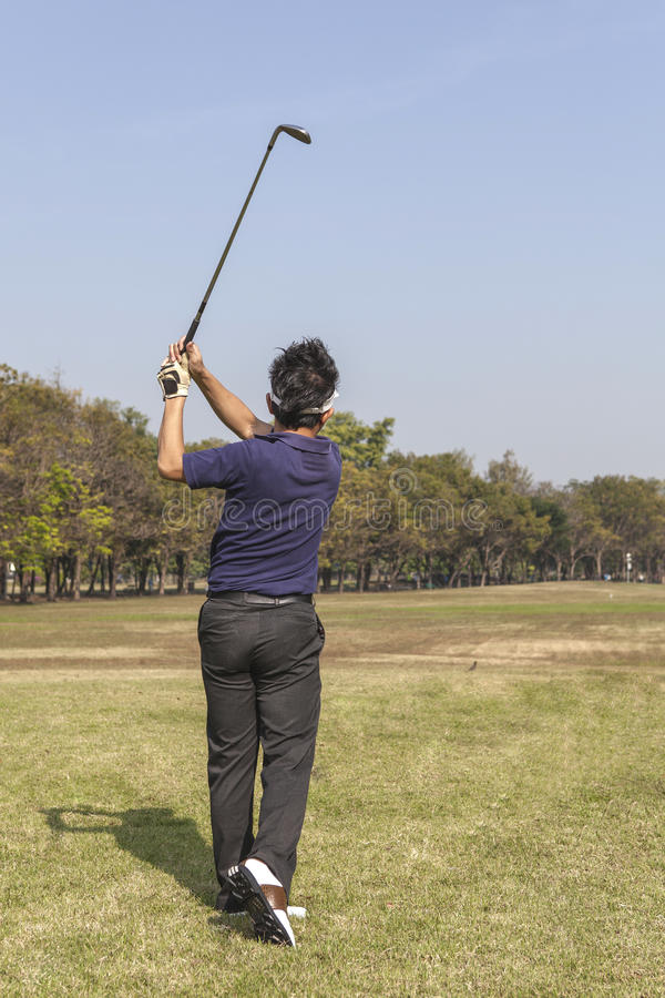 Male golf player teeing off golf ball from tee box. Wonderful cloud formation in background royalty free stock images