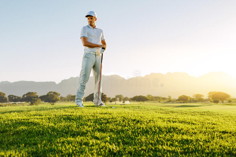 Male golfer with golf club on field looking away stock photography