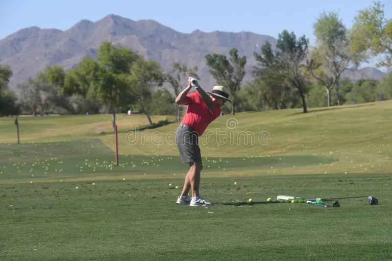 Male golfer hitting a golf ball from a back view. royalty free stock photo