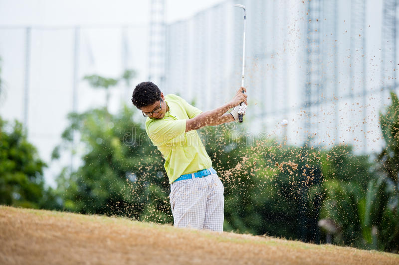 Male golfer hitting golf ball out of a sand trap. With sand wedge and sand caught in motion royalty free stock photos