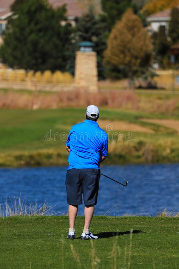 Male golfer on a residential golf course fairway with a lake and homes in the background royalty free stock photography