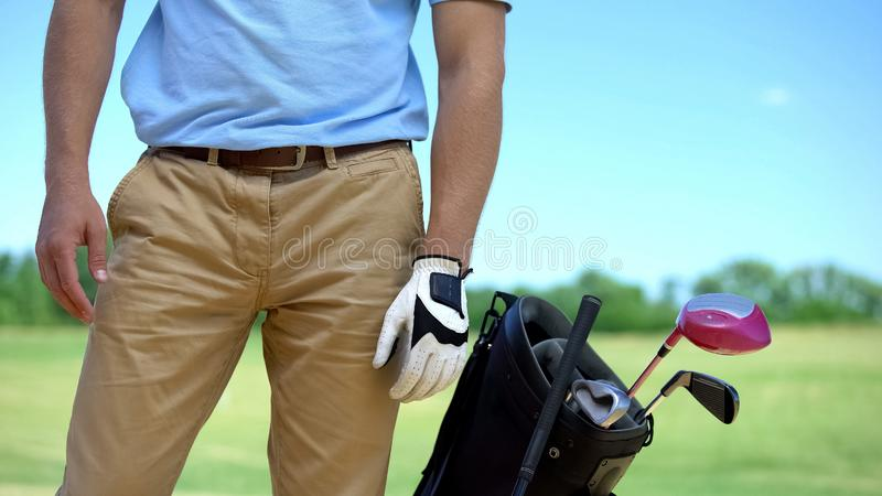 Male golfer in white glove before game, bag with sport equipment nearby, sport royalty free stock photography