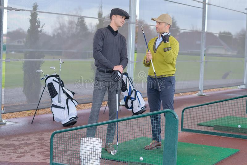 Male golfers communicating at golf training stand. Golf stock photo
