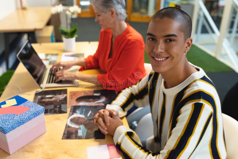 Male graphic designer looking at camera while coworker using laptop in the background. Portrait of mixed race male graphic designer looking at camera while royalty free stock image