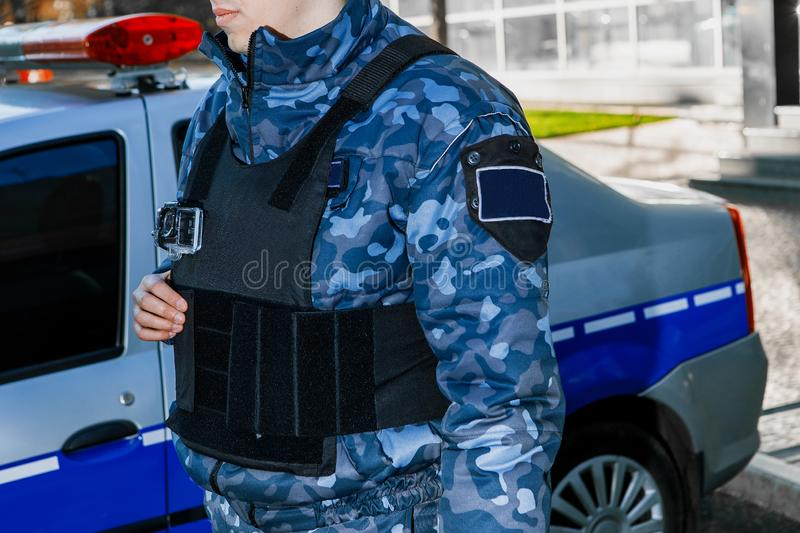 A male security guard in full gear is standing next to a company car. A male guard in full gear is standing next to an official car with signal lights royalty free stock image