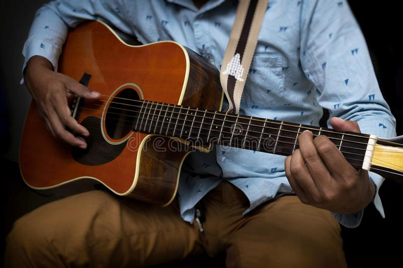 Male Guitar Musician Playing His Acoustic Guitar iSolated Black Background stock photo