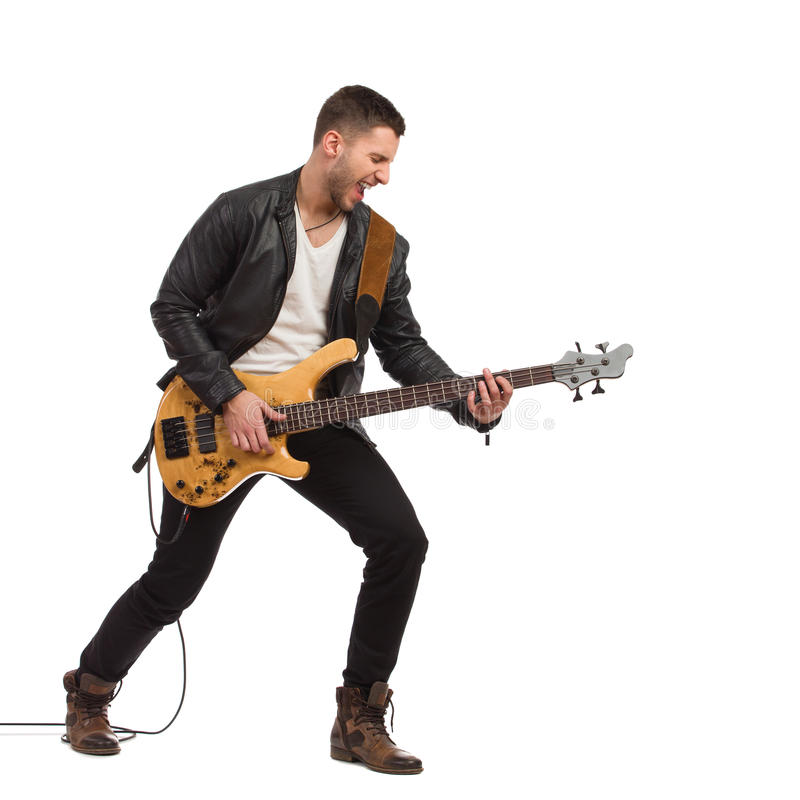 Male guitarist with bass guitar. Shouting guitarist in black leather jacket plays the bass guitar. Full length studio shot isolated on white royalty free stock photography