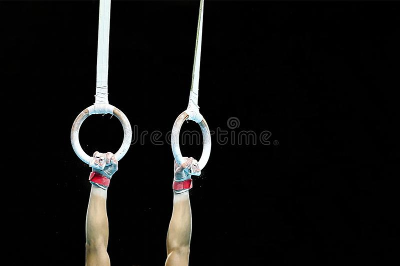 Male gymnast hands holding the rings stock photography