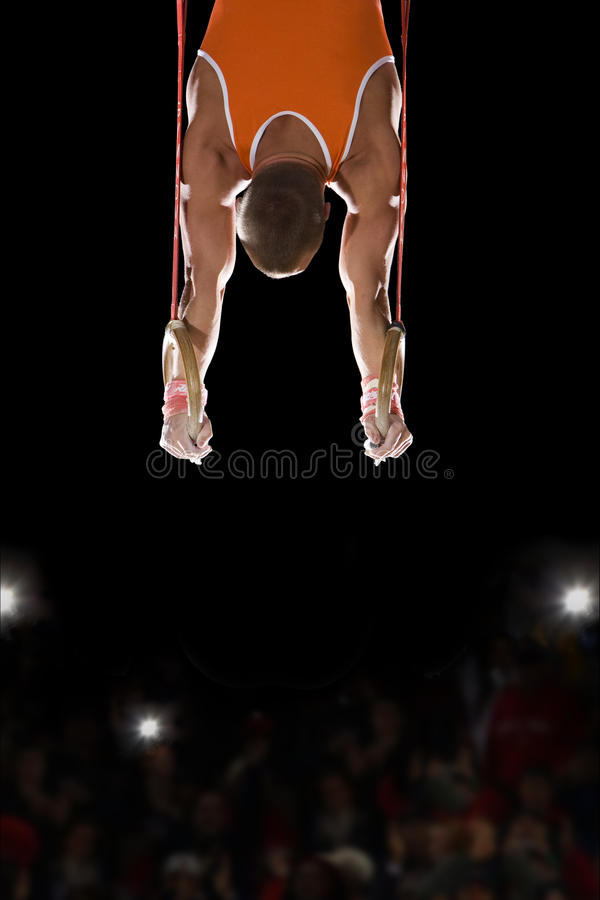 Male gymnast performing on gymnastic rings, rear view stock image