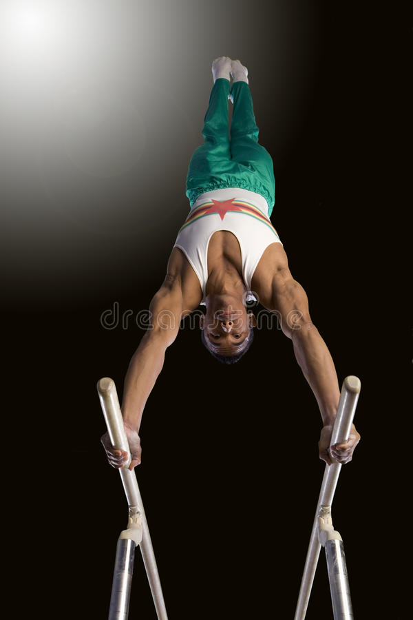 Male gymnast performing handstand on parallel bars, low angle view royalty free stock image