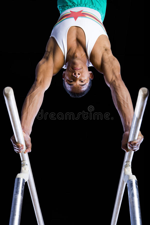 Male gymnast performing on parallel bars, low angle view stock photography