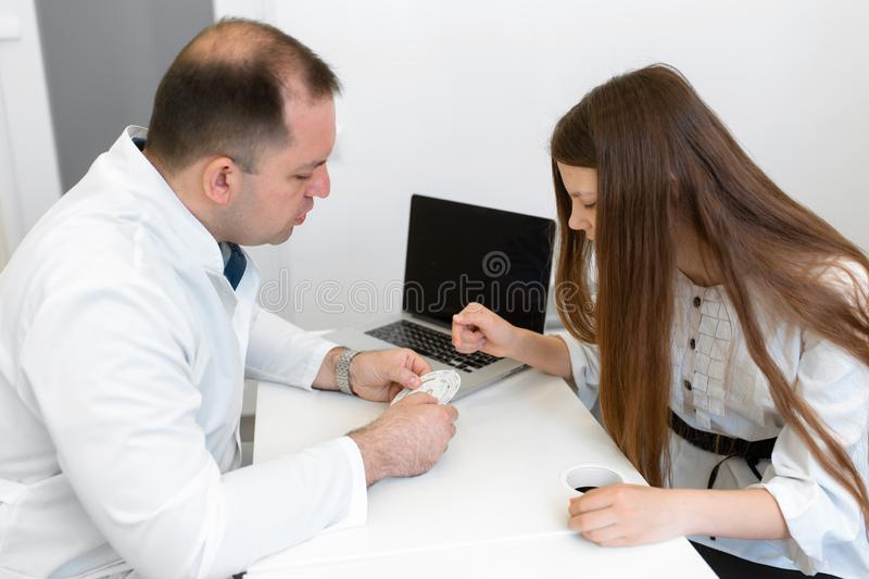 A male gynecologist consults a young girl about the menstrual cycle, showing the menstrual calendar. Professional medical stock photo