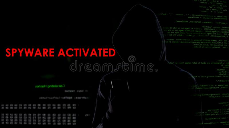 Male hacker activating spyware on smartphone, collecting private information royalty free stock photography
