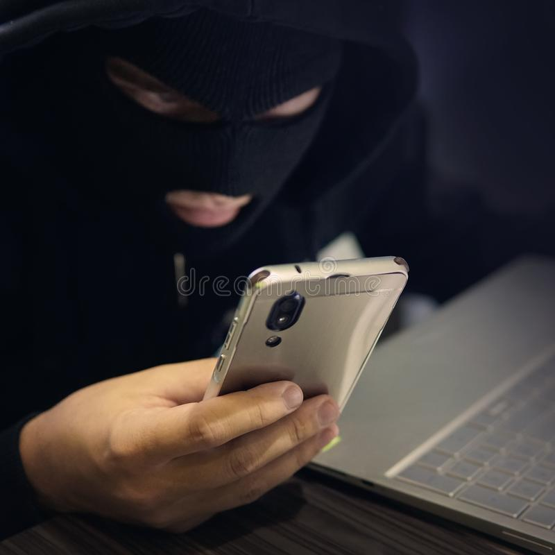 Male hacker in a black mask uses smartphone and laptop. A fraudster commits cyber crime. Fraudulent scheme with personal data and. Banking. Attempt to make royalty free stock photography