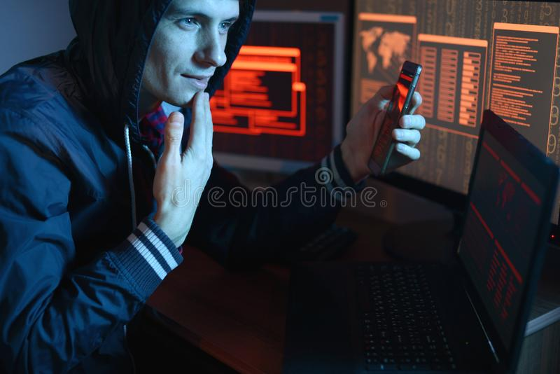 Male hacker in the hood holding the phone in hands trying to hack the mobile device cloud in the dark under neon light. Male hacker in the hood holding the phone royalty free stock photo