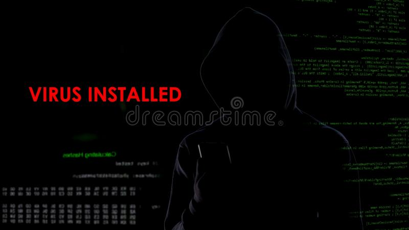 Male hacker installed virus on enemy laptop, malicious software computer program stock images