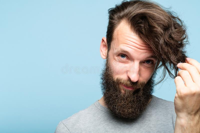 Male hair styling fashion problem haircare product. Male hair styling problems because of modern long hairdo fashion. haircare products concept. bearded hipster stock photography