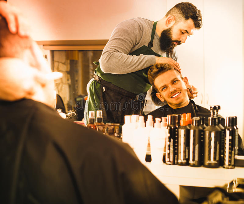 Male hairdresser accurately cutting beard. Young cheerful positive male hairdresser accurately cutting beard of client at hair salon stock images