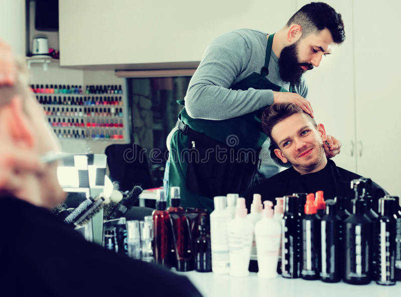 Male hairdresser accurately cutting beard. Young glad cheerful male hairdresser accurately cutting beard of client at hair salon stock image