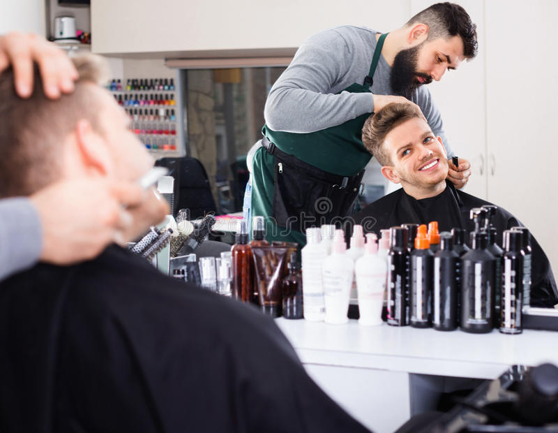 Male hairdresser accurately cutting beard. Young positive male hairdresser accurately cutting beard of client at hair salon royalty free stock photo