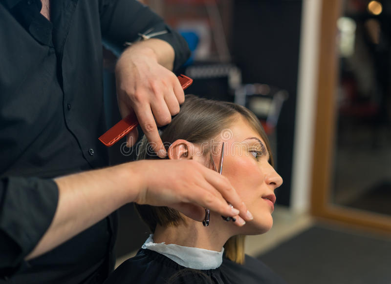 Male hairdresser does a haircut to pretty woman royalty free stock photos