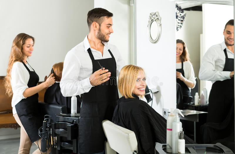 Male hairdresser making haircut stock photography