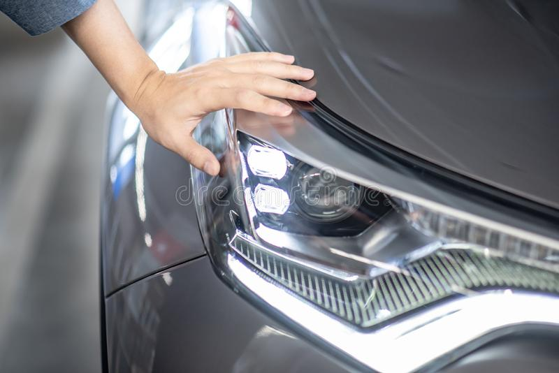 Male hand auto mechanic checking car headlight. Male hand auto mechanic checking headlight in auto service garage. Mechanical maintenance engineer working in royalty free stock images