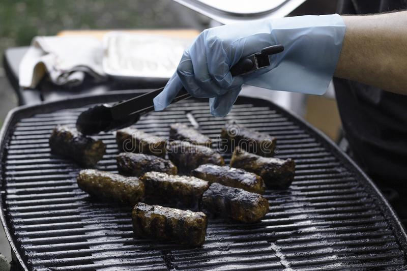 Male hand with blue plastic glove by outdoor grill. Close up of the hand of a male, wearing a blue plastic glove holding a kitchen tong, while turning the meat stock image