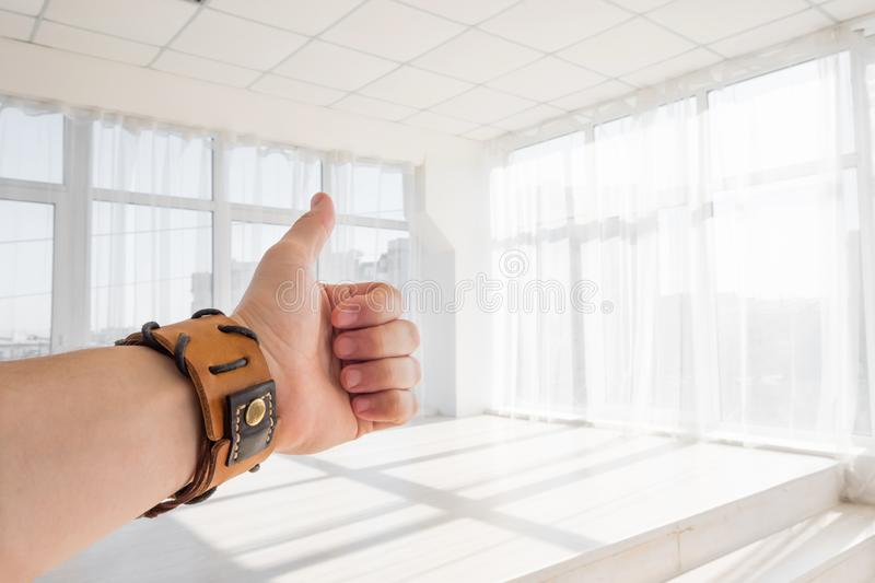 Male hand showing thumbs up sign against white background royalty free stock photography