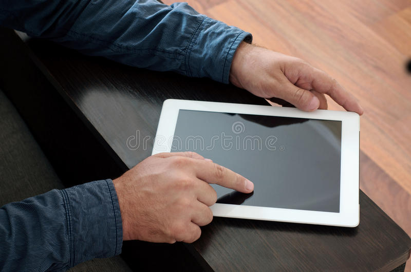 Male hand click on a blank screen tablet computer closeup. Top view royalty free stock photography