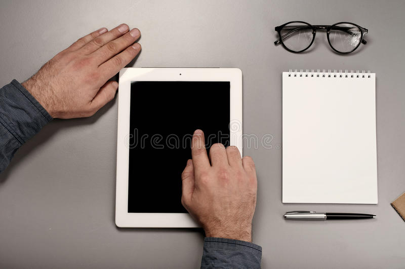 Male hand click on screen tablet computer. Man working with a tablet computer. Male hand click on screen tablet computer closeup. Top view stock image
