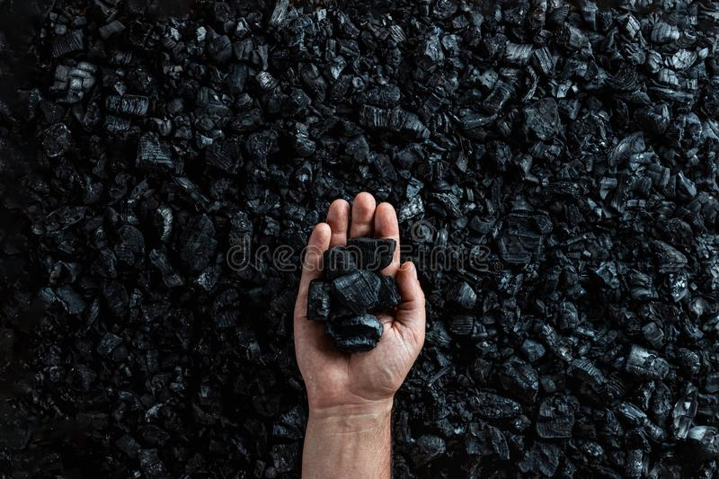 Male hand with coal on the background of a heap of coal, coal mining in an open pit quarry, copy space. Fossil fuels, royalty free stock photos