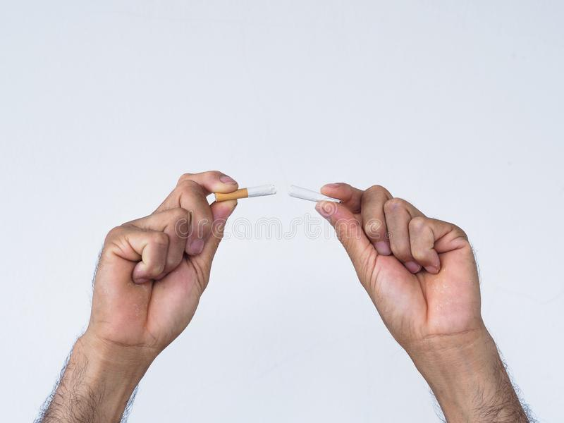 Male hand crushing cigarette on white background, Concept Quitting smoking,World No Tobacco Day. stock image