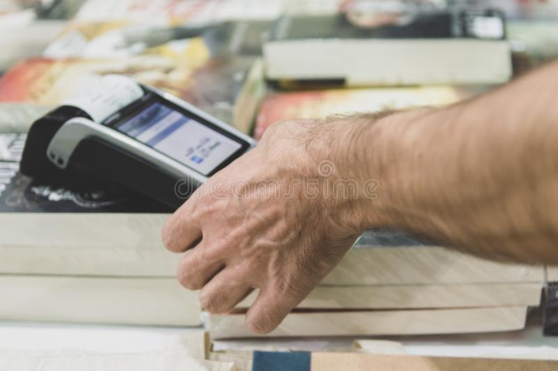 Male hand dialing pin code on pin pad of POS machine. Close up of male hand using credit card swiping machine to pay. Man entering credit card code in POS stock photo