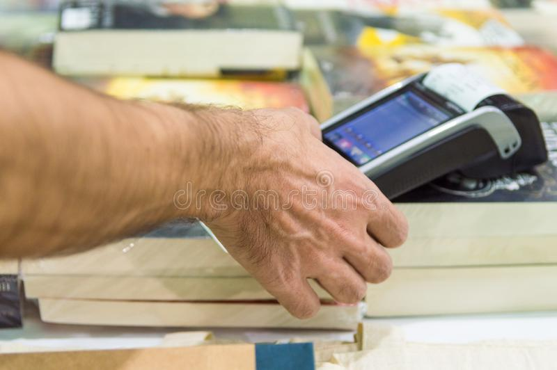 Male hand dialing pin code on pin pad of POS machine. Close up of male hand using credit card swiping machine to pay. Man entering credit card code in POS stock photos