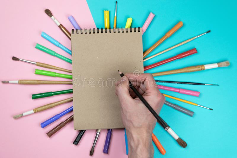 Male hand drawing, blank paper and colorful pencils. Branding stationery mockup scene, blank objects for placing your design. stock photos