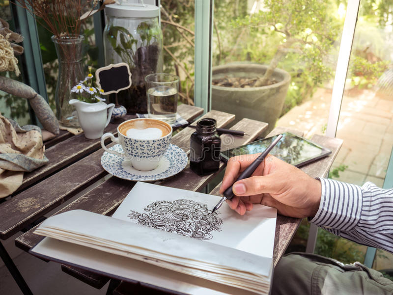 Male hand drawing doodle line art on paper with coffee and table royalty free stock image
