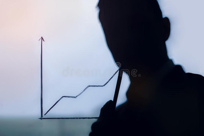Male hand drawing a graph. Business development to success and growing growth concept, Businessman pointing arrow graph corporate. Business development to stock images