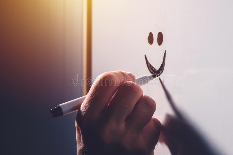 Male hand drawing smiley emoticon on office whiteboard. Happy satisfied businessman during business results presentation, selective focus royalty free stock image