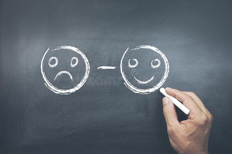 Male hand drawing unhappy and happy smileys faces on chalkboard.  royalty free stock images
