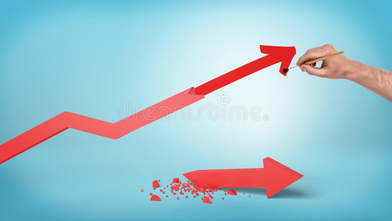 A male hand draws a new point for a red statistic arrow instead of a broken and a fallen one. royalty free stock photography