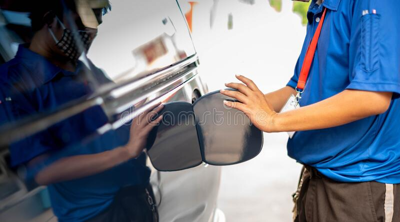 Male hand fill up petrol tank gasoline fuel petrol in car being filled with fuel at gas petrol station.  stock photos
