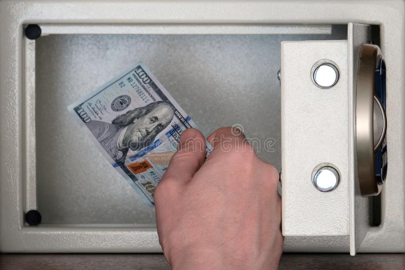 The male hand folds one hundred US dollar bill into an individual safe deposit box. The concept of saving money, service in a royalty free stock photography