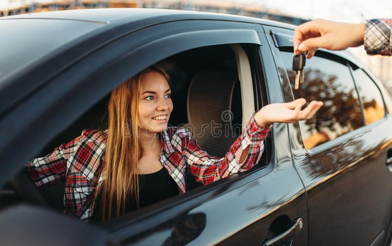 Male hand gives the car keys to female driver. Male hand gives the car keys to cheerful female beginner driver after exam, successful end of car school concept stock photography