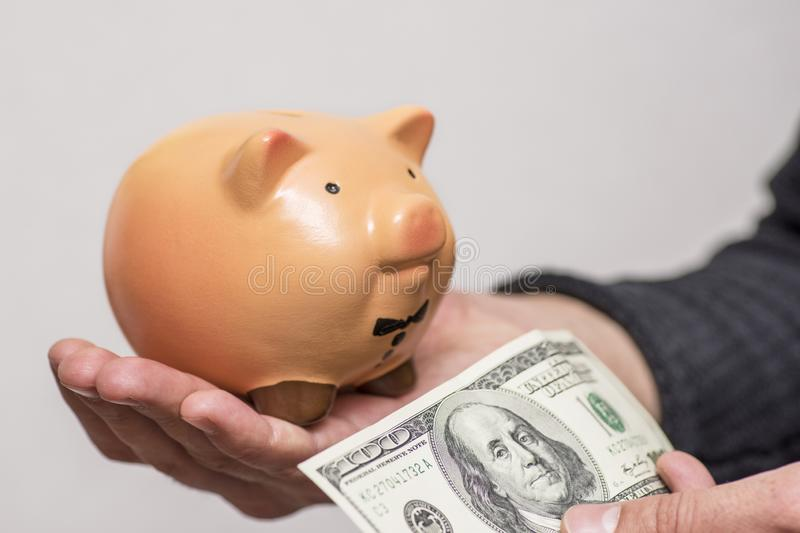 Male hand gives 100 dollar bill piggy bank. Male hand saving money in a piggybank. Save money concept.  stock photo
